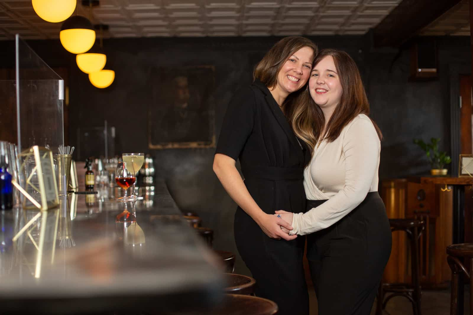 Two women hug standing next to a dimly lit cocktail bar