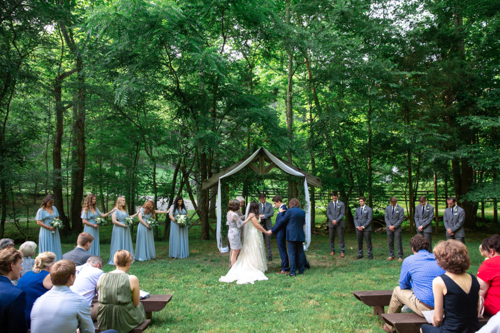 Prayer ceremony with bride and groom under a wooded arbor in Tennessee Outdoor Farm Wedding
