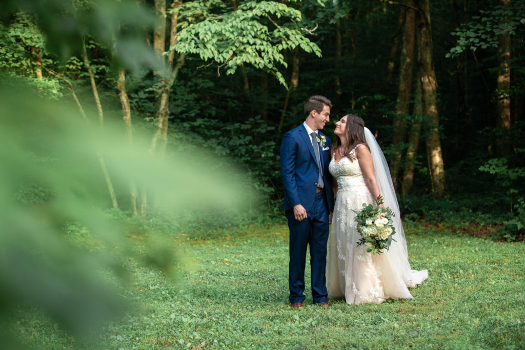 Bride and groom walking near woods in Tennessee Outdoor Farm Wedding