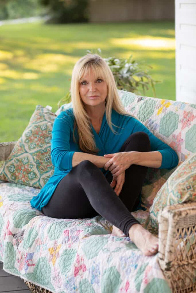 blonde woman sitting with legs up on a porch sofa on a quilt
