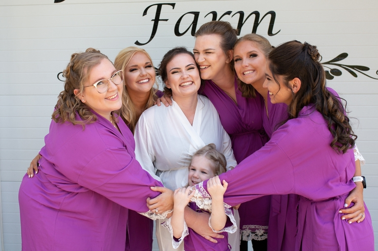 Bride and bridesmaids laughing and wearing purple robes at Nashville farm wedding